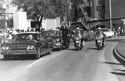 Said to have been taken between the second and third shots fired at Kennedy, this photo shows the agents on the right side of the follow-up vehicle turning to look back towards the sound of the shots.