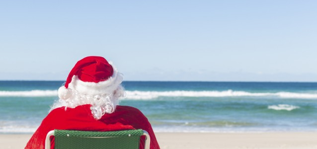 Santa relaxing on an Australian beach with his feet up